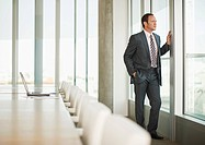 Pensive businessman standing at window of empty conference room