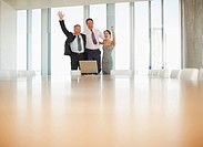 Excited business people celebrating in front of laptop in conference room