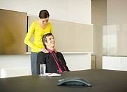 Businesswoman rubbing businessman's shoulders in conference room