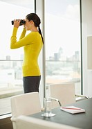 Businesswoman with binoculars looking out office window
