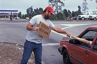 USA, Florida, Man holding out of work sign to passing motorist