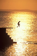 Brazil, Salvador Bahia, The Barra, Young boy jumping in ocean at sunset