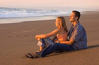 Teenage couple on beach watching the sunset,Pacific Ocean , California