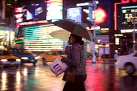 USA, New York City: People carrying umbrellas on rainy night in Times Square