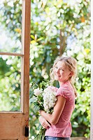 Smiling girl holding bouquet of flowers in doorway