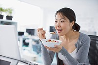 Businesswoman eating cereal and looking at laptop in office