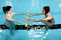 Women in swimming pool doing pilates exercise