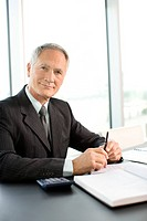 Smiling businessman sitting at desk in office