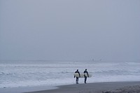 Two surfers walking at dusk along the beach in Oceanside California