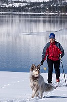 A woman and dog skiing on the shore of Donner Lake in winter near Truckee, California