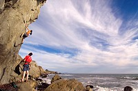 A man and a woman rock climbing next to the Pacific Ocean at Mickey´s Beach near Stinson Beach in California