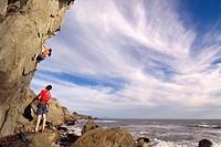A man and a woman rock climbing next to the Pacific Ocean at Mickey´s Beach near Stinson Beach in California