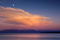 The full moon and a thunderhead cloud over Lake Tahoe, California at sunset