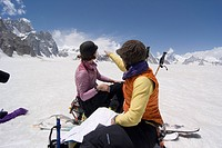 Two women ski mountaineers reading a map at Snow Lake on the Biafo glacier in the Karakoram himalaya of Pakistan