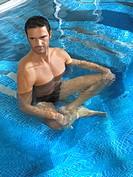 Man in swimming pool doing yoga