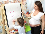 Pregnant mother drawing with son
