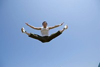Young man jumping and doing splits in mid air