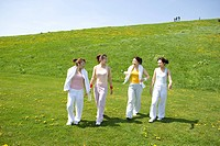 Four young women walking in field