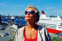 Sexy looking blond Swedish woman in Stockholm with docked Viking Line passenger ship