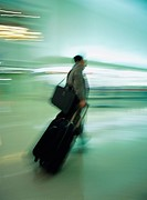 Man walking with luggage at airport, blurred motion