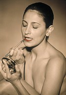 Nude woman applying lip mascara using small mirror