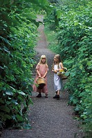 Two young girls on narrow pathway with baskets of flowers in summer