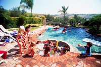 Kids playing in backyard swimming pool and jacuzzi