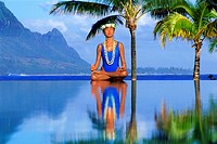 Woman in yoga position on poolside at Hanalei Bay on Kauai Island in Hawaii