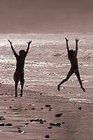 Kids age 10 & 13 playing in the surf on Sand Dollar Beach silhouette, Big Sur Coast, California