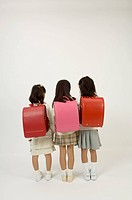 Three elementary age girls standing, rear view