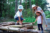 Boy standing on logs and family watching