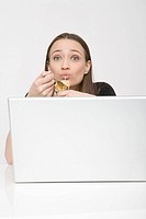 Young woman in front of laptop eating spaghetti from can