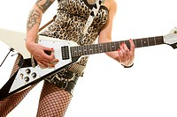 Sexy, alluring, tattooed woman in fishnet stockings playing electric guitar