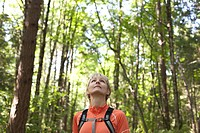 Caucasian woman looking at sky during hike in forest