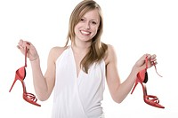 Young woman holding a pair of red shoes