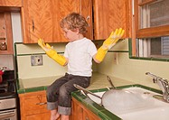 Boy sitting on kitchen counter wearing latex gloves