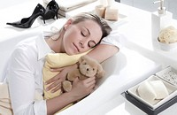 Woman sleeping in bathtub