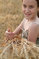 Girl holding bunch of wheat