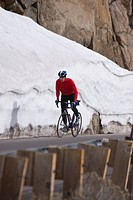 A man climbing uphill on a bicyle in winter on Donner Summit in California