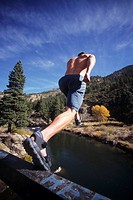 Young man jumping off ledge into the Truckee River, California, USA