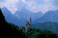 GERMANY, BAVARIA, NEAR FUSSEN, NEUSCHWANSTEIN CASTLE, WITH MOUNTAINS IN BACKGROUND, THE ALPS