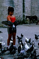 CUBA, OLD HAVANA, PLAZA SAN FRANCISCO, GIRL FEEING PIGEONS
