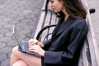 Young woman sitting on bench with laptop