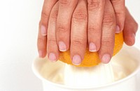 Hands with citrus fruit on juice reamer,close up