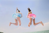 Two young women in bikini jumping