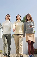 Three young women walking front yard