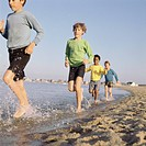 Group of four boys running along the sea shore