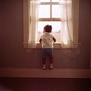 Little girl looking out the window hanging from the window ledge inside