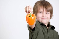 Boy holding an orange pepper in his hand