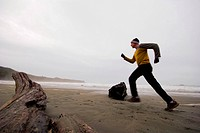 Low angle motion blurred view of man running on the beach in winter, Tofino area, BC, Canada